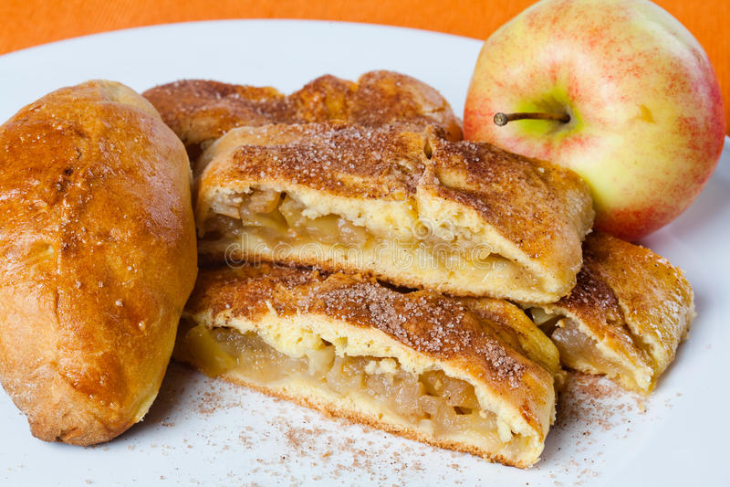 Jabłczanego kulebiaka i torta plasterki na bielu talerzu, domowej roboty piec deser Pomarańczowy tło fotografia royalty free