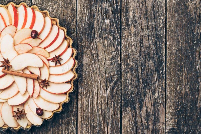 Jabłczanego kulebiaka tarta na nieociosanym drewnianym tle Składniki - jabłka i cynamon Odgórny widok fotografia stock
