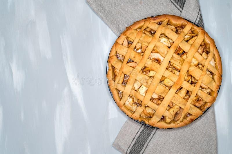 Jabłczanego kulebiaka tarta z rodzynkami, dokrętkami i cynamonem na rocznika tła drewnianej teksturze, Tradycyjny deser dla dnia  fotografia royalty free