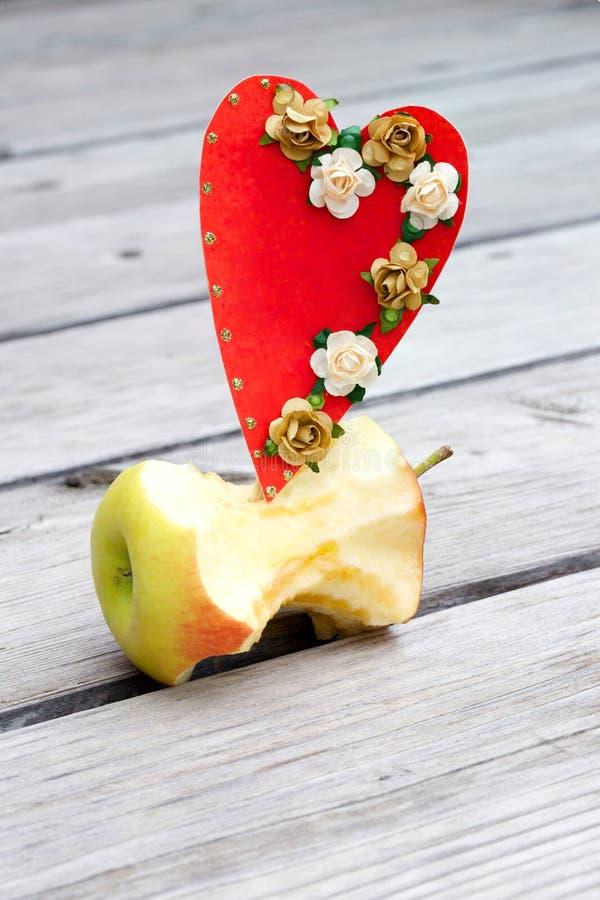Jabłczany sedno i czerwony kartonu serce obrazy royalty free