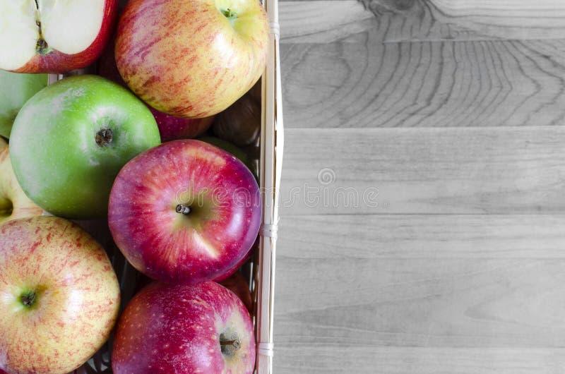 Jabłka czerwień i zieleń w koszykowym odgórnego widoku czerni bielu tle zdjęcia royalty free