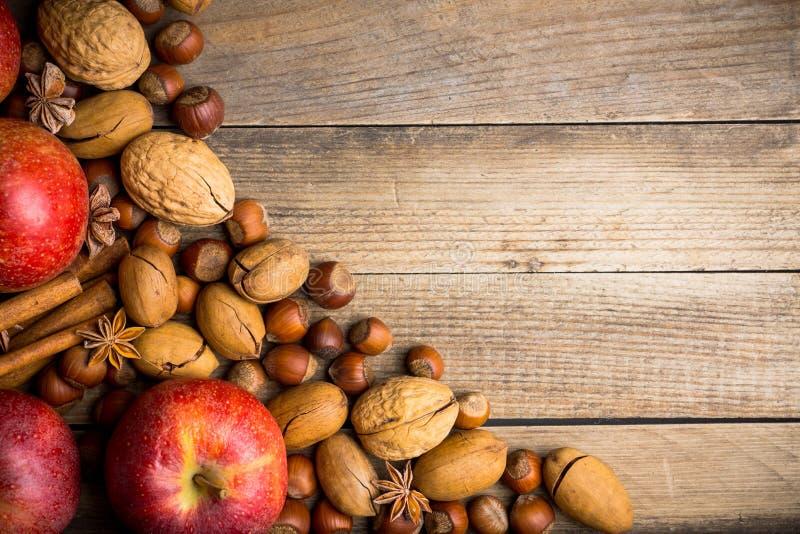 Jabłka, dokrętki i pikantność na drewnianym tle, obrazy stock