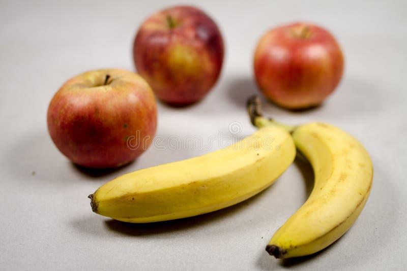 Jabłka i banany na Szarym bielu Siwieją marmuru Łupkowego tło obraz royalty free