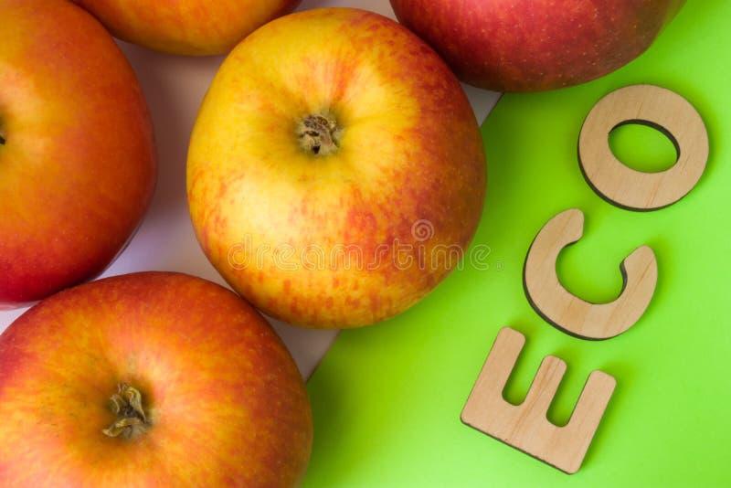 Jabłka jako ECO jedzenie Jabłka są na białym tle z teksta eco drewniani listy na zieleni Przykład podtrzymywalny environmentall fotografia stock
