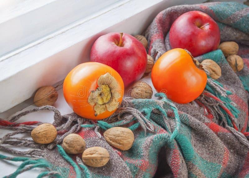Jabłka, persimmons, orzechy włoscy i stara chusta, obraz stock