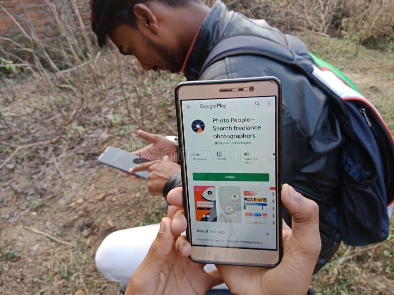 jabalpur, Indien - Dezember 2019: auf dem Smartphone-Bildschirm angezeigte App für Fotomenschen mit feststehendem Mobiltelefon lizenzfreie stockfotografie