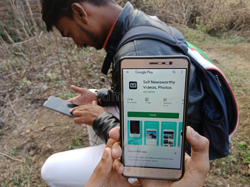 jabalpur, Indien - Dezember 2019: verkaufsfördernde Video-App auf Smartphone-Bildschirm mit festem Mobiltelefon stockbild