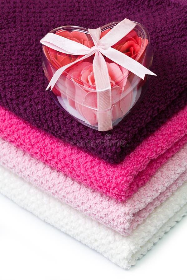 Jabone las rosas de la espuma en un rectángulo en forma de corazón en las toallas de baño imágenes de archivo libres de regalías
