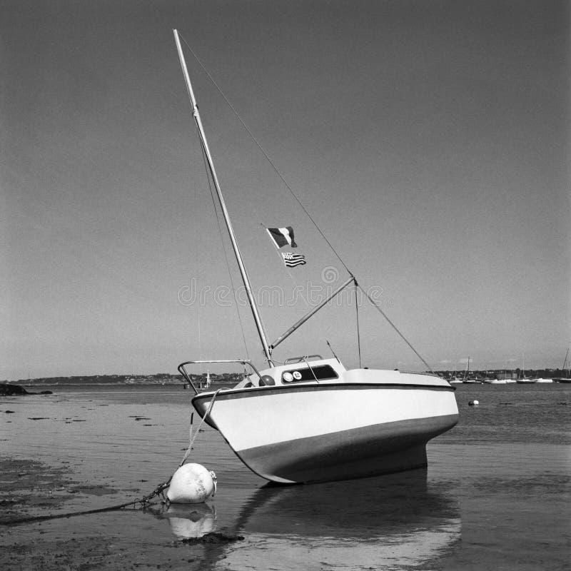 Jacht bij zandmoorage at low tide stock afbeeldingen