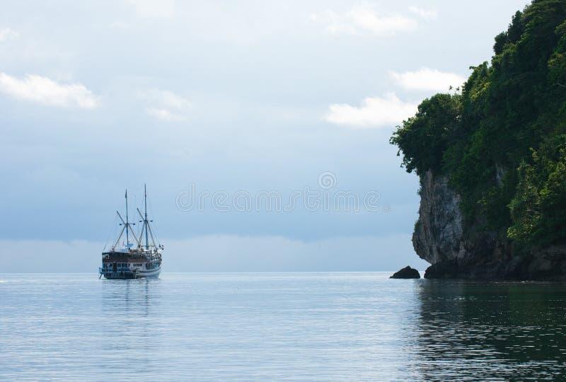 Jacht dat naast rotsachtig eiland vaart royalty-vrije stock afbeelding