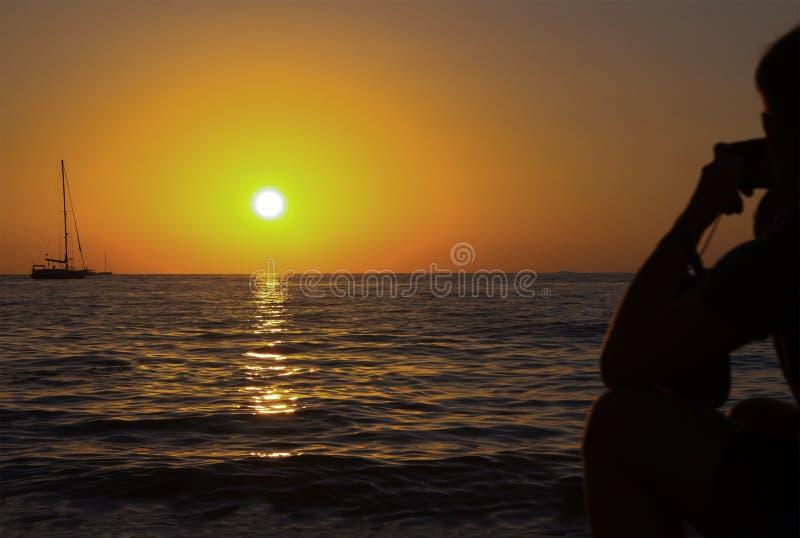 Jacht die het heldere silhouet van de zonsondergang gouden zon van een mens op de kust varen die de afstand op een schip in het o stock afbeeldingen