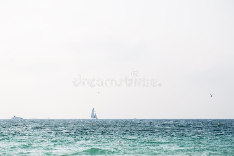 Jacht na horyzoncie przy morzem z niebieskim niebem i chmurami fotografia stock