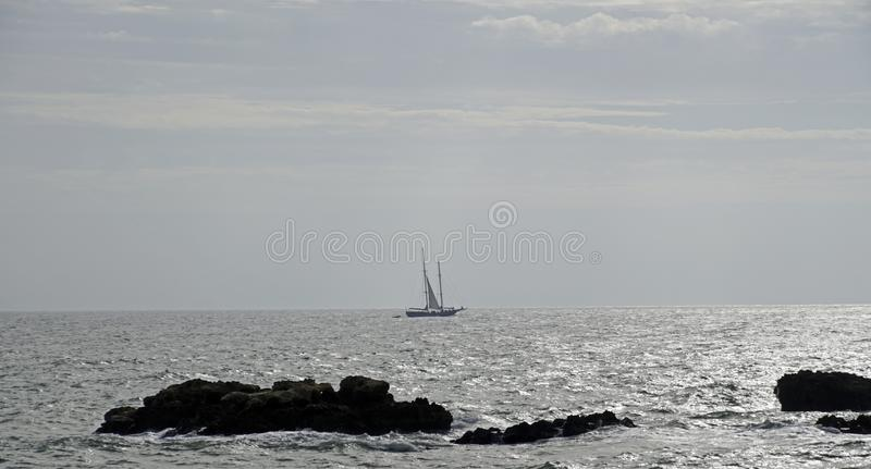 Jacht op de horizon onder zeil Heldere zon over de oceaan stock fotografie