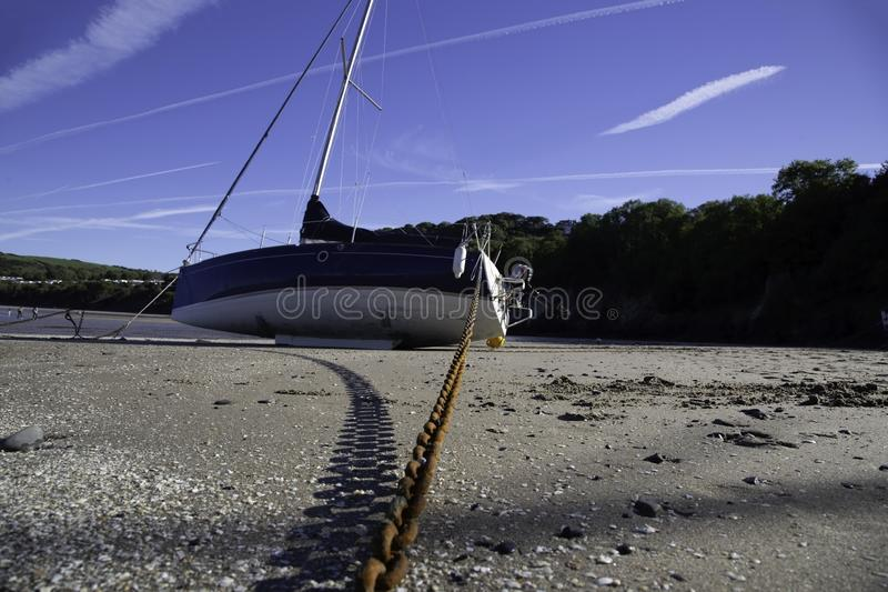 Jachtboot op een zandig die strand met een roestige ketting wordt gebonden stock afbeeldingen