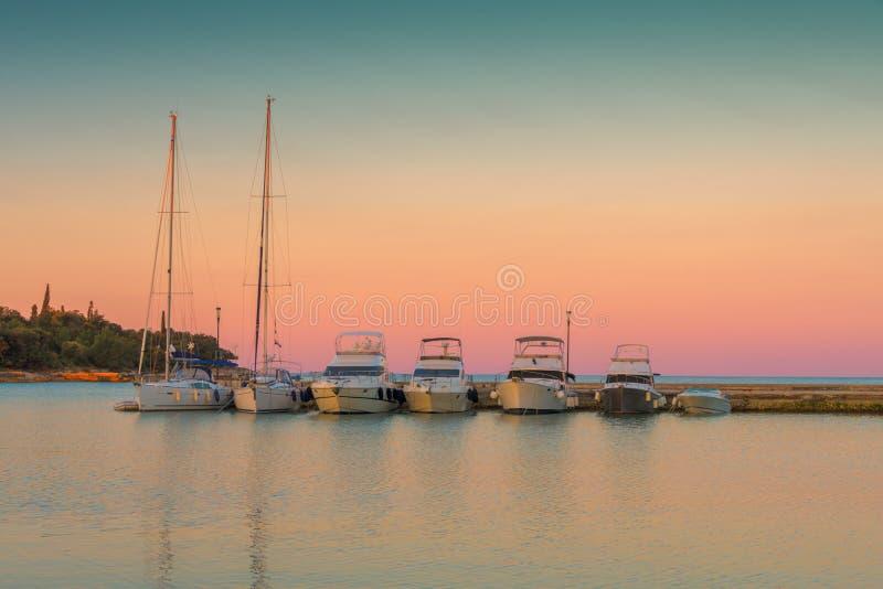Jachten en boten die in kleine haven in Kroatië in beautityful ochtendzonsopgang parkeren stock foto's