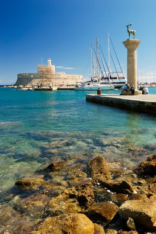 Jachten en oude vuurtoren in de haven van Rhodos royalty-vrije stock foto
