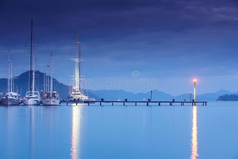 Jachthaven bij nacht met vastgelegde jachten stock fotografie