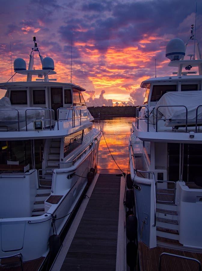 Jachthavendok met te grote luxeboten bij schemer stock fotografie