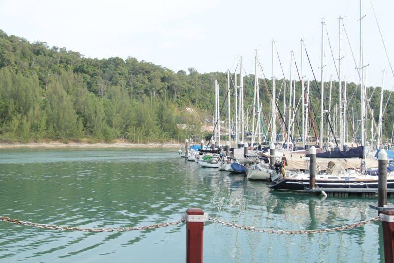 Jachthavenpier met zeilboten dichtbij heuvelsachtergrond stock afbeelding