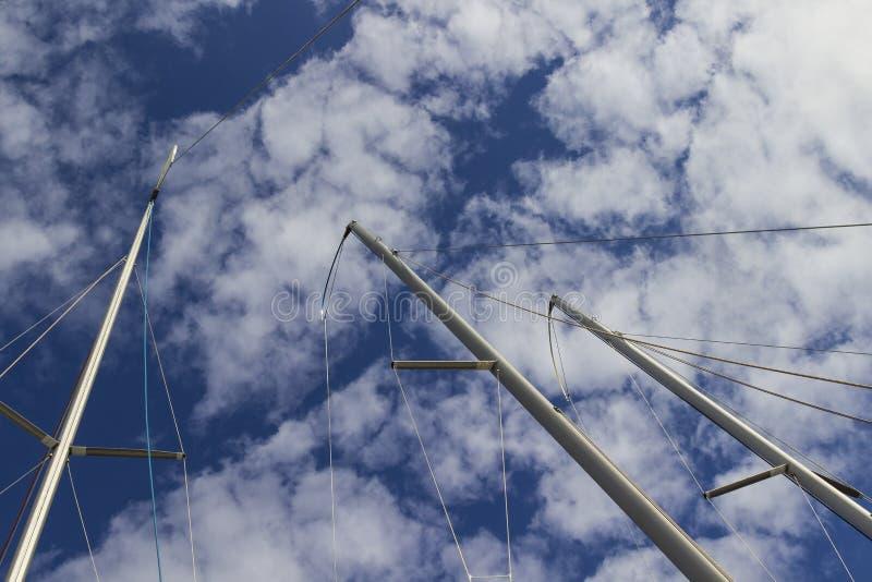 Jachtmasten hoog in de blauwe hemel met grote witte cumuluswolken royalty-vrije stock foto's
