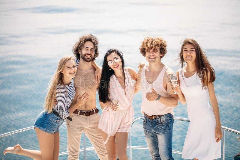 Jachtpartij met jongeren die een bootpartij hebben, die op een boog van jachtdek dansen stock foto's