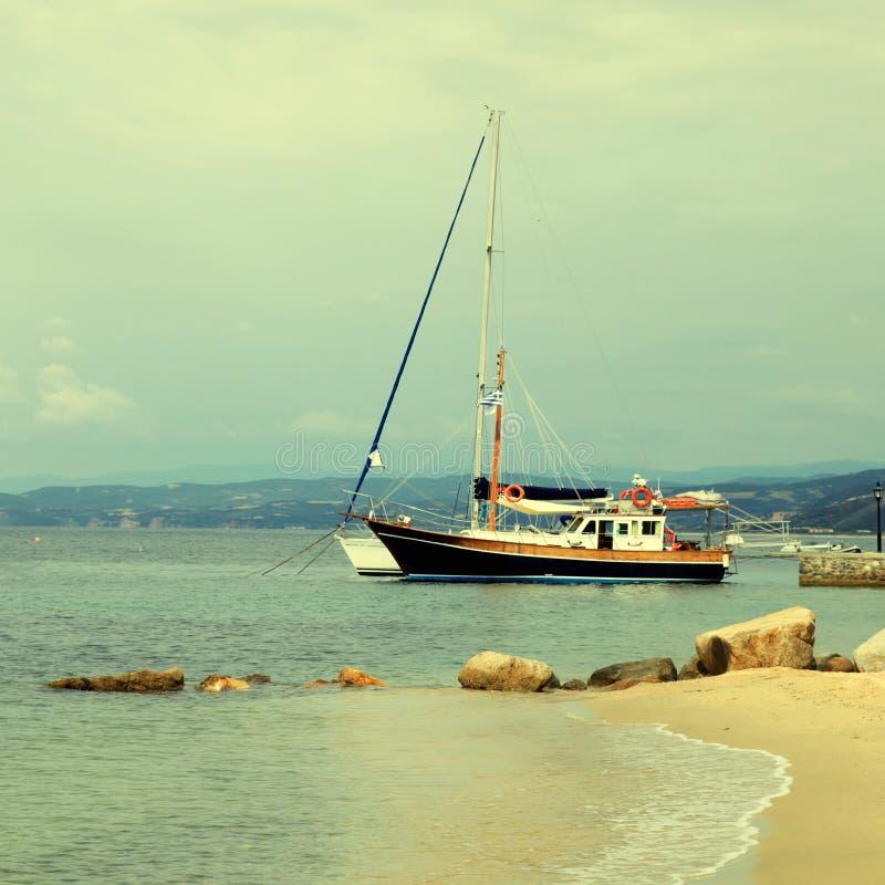 Jachtu łodzie, molo i piasek, wyrzucać na brzeg, morze śródziemnomorskie, Grecja obrazy stock