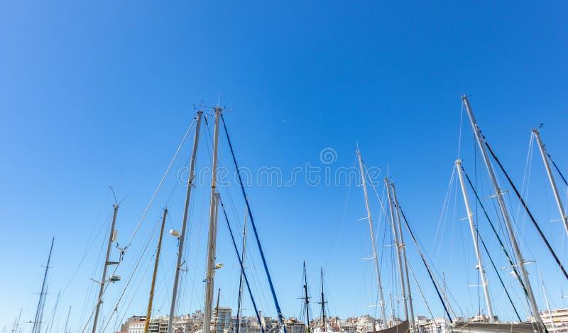Jachtu masztu wierzchołki przeciw jasnemu niebieskiemu niebu przy marina Zeas, Grecja Pionowo linie z arkanami, miasta tło obrazy stock
