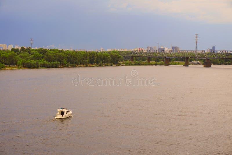 Jachtu statek, łódź iść na powierzchni Zaporoski Dnipro, Dnepr rzeka przeciw tłu miasto drapacze chmur obraz royalty free