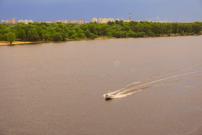 Jachtu statek, łódź iść na powierzchni Zaporoski Dnipro, Dnepr rzeka przeciw tłu miasto drapacze chmur zdjęcie stock