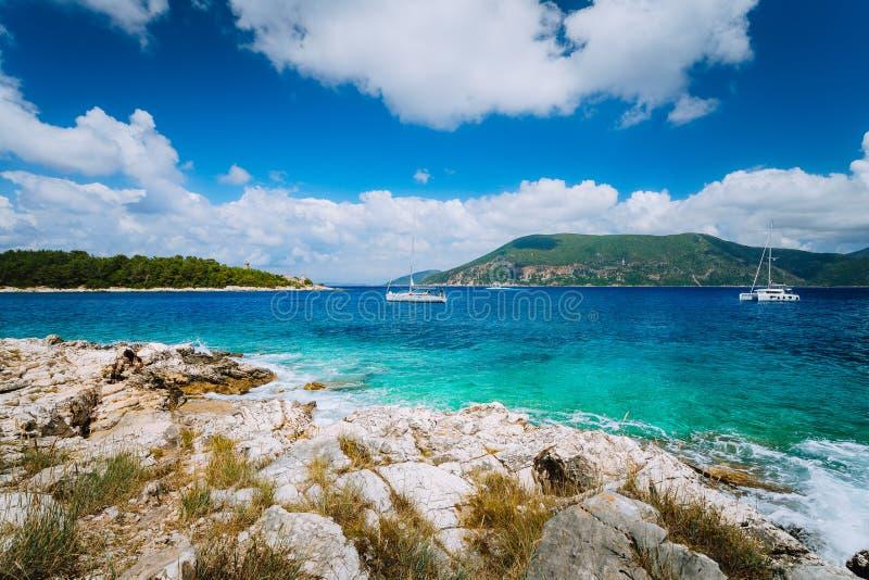 Jachty dryfują w środku otwarty kryształ - jasna szmaragdowej zieleni woda morska blisko Fiskardo miasteczka Ithaki wyspa w tle zdjęcia stock