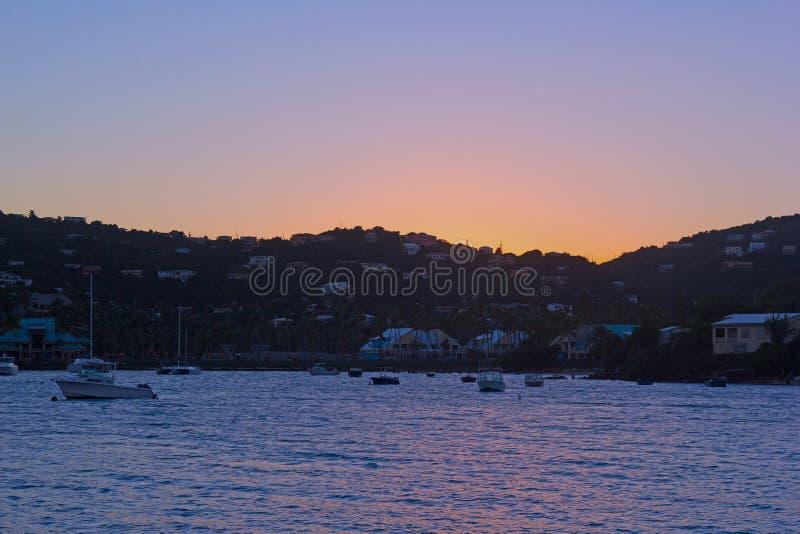 Jachty i motorboats cumujący przy St Tomasowską wyspą trzymać na dystans przy zmierzchem po długiego dnia przy morzem zdjęcia stock