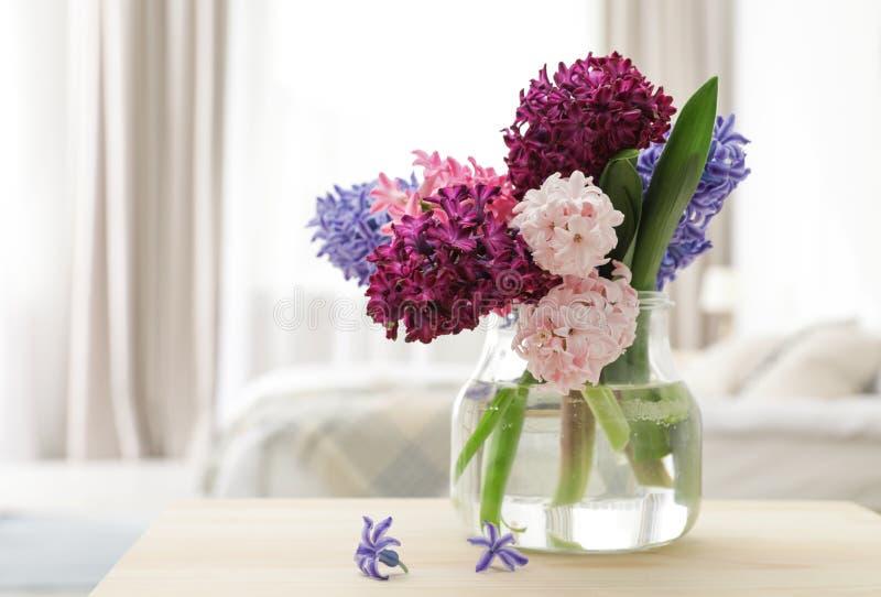 Jacintos hermosos en el florero de cristal en la tabla dentro, espacio para el texto fotos de archivo