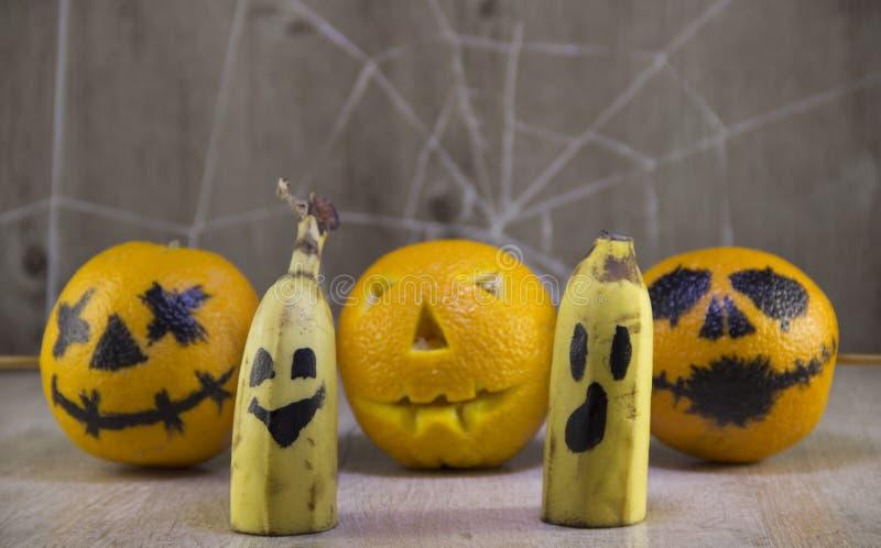 Jack-Laterne für Halloween von Orangen auf einem hölzernen Hintergrund mit Spinnennetzen lizenzfreie stockbilder