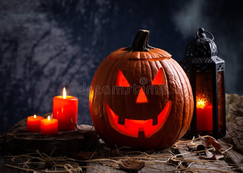 Jack O Lantern With burning Candles and Lantern. Glowing Jack-O-Lantern with burning candles and lantern on a wooden surface and dark background stock photography