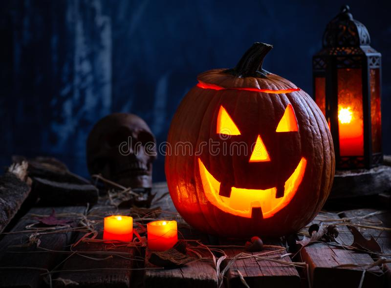 Jack-O-Lantern With Candles and Lantern. Jack-O-Lantern with burning candles and lantern on a rustic wooden surface and spooky background royalty free stock photo