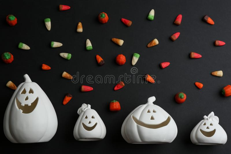 Jack-o-Lantern candle holders and jelly candies on black background. Halloween decor. Jack-o-Lantern candle holders and jelly candies on black background, flat royalty free stock images