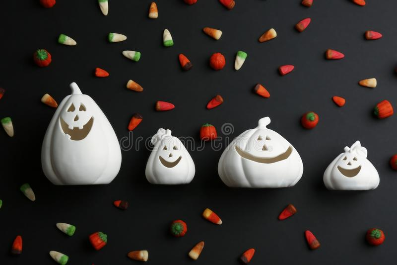 Jack-o-Lantern candle holders and jelly candies on black, flat lay. Halloween decor. Jack-o-Lantern candle holders and jelly candies on black background, flat stock photography