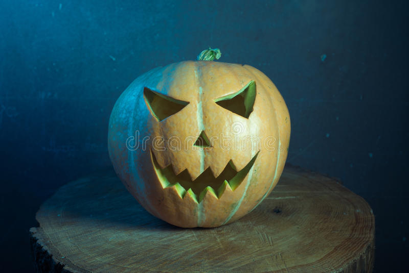 Jack-o ' - lantern in cool tones. On a wooden background, three-dimensional and bright light royalty free stock photos