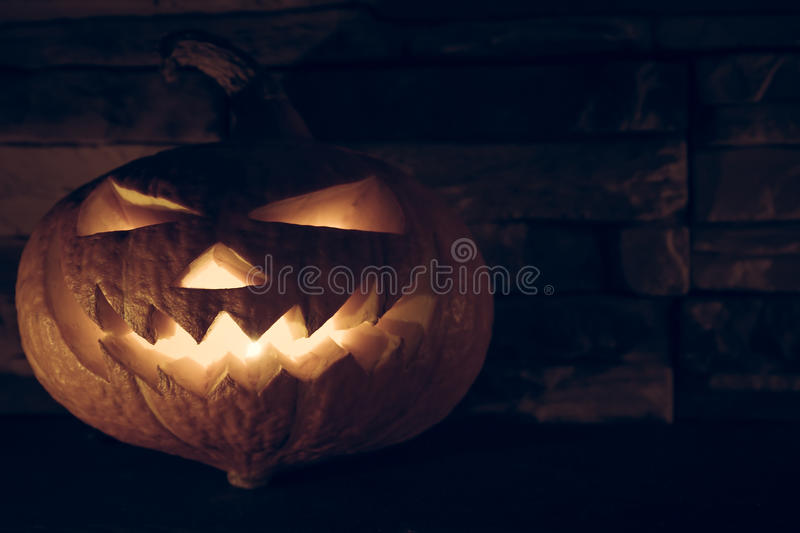 Jack O' lantern with luminous devil smile for halloween in darkness on stone background royalty free stock images