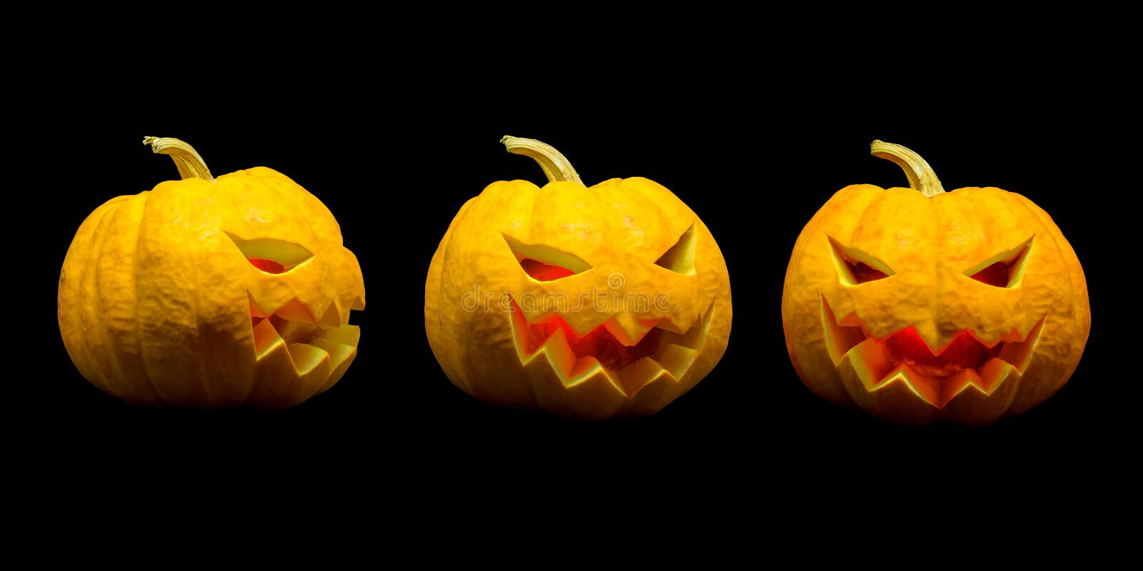 Jack o lantern pumpkin faces with lights on black background for Halloween season.  stock photography