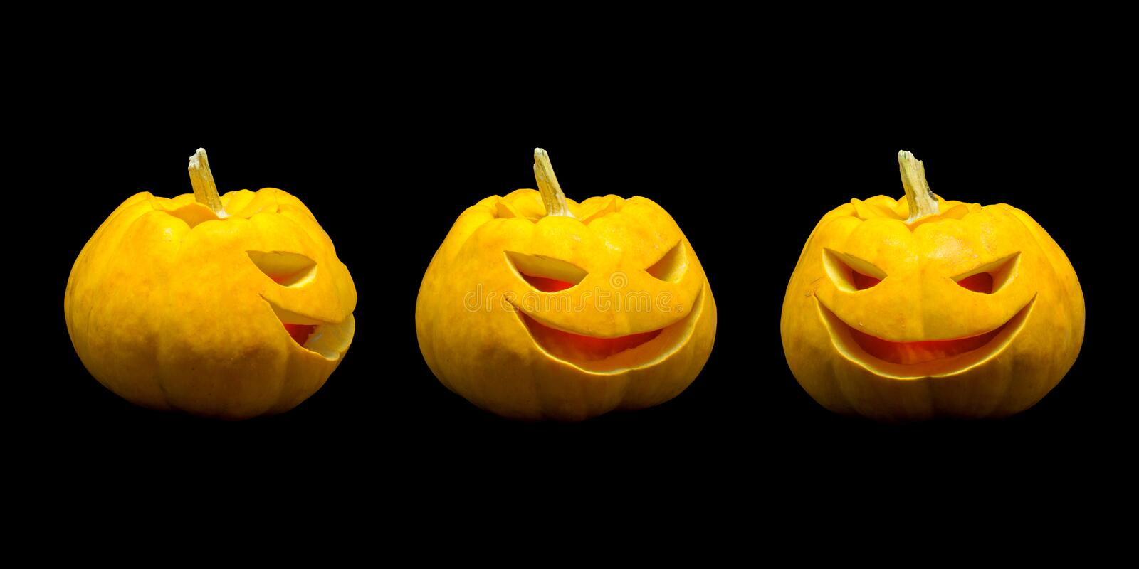 Jack o lantern pumpkin faces with lights on black background.  royalty free stock photos