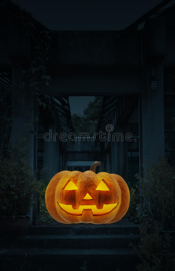 Jack O Lantern pumpkin on floor of old damaged building stock photo