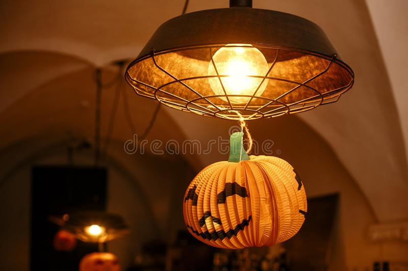 Jack o lantern pumpkin hanging on lamp in city street, holiday decoration of store fronts. Halloween street decor. Space for text stock images