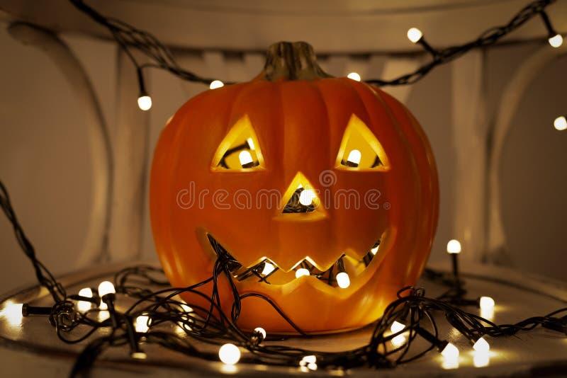 Jack o Lantern pumpkin with light garland on dark. Happy halloween. Jack o Lantern pumpkin with light garland on dark background royalty free stock image