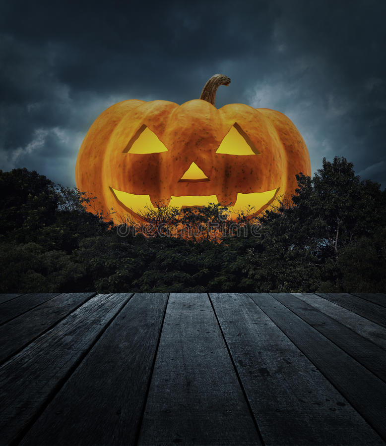 Jack O Lantern pumpkin with old wooden table, tree over spooky c royalty free stock images