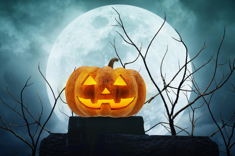 Jack O Lantern pumpkin on the rock over dead tree and moon stock photo