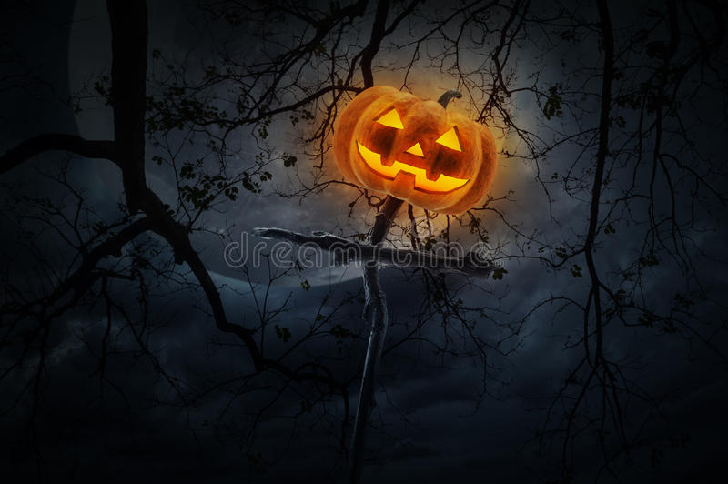 Jack O Lantern pumpkin on wood cross over dead tree, moon and cl royalty free stock photo