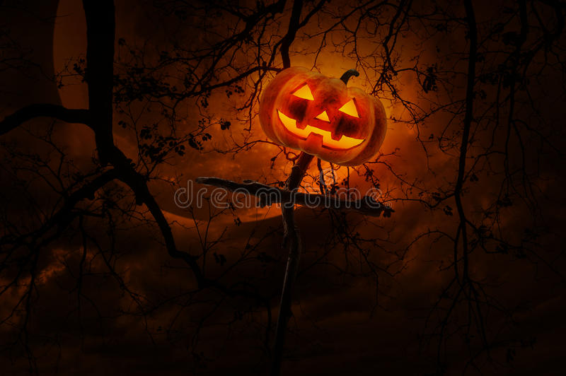Jack O Lantern pumpkin on wood cross over dead tree, moon and cl royalty free stock photography