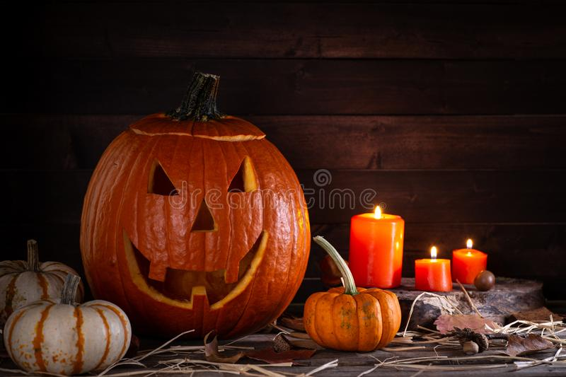 Jack-O-Lantern With Pumpkins and Candles. Jack-O-Lantern with mini pumpkins and burning candles on a rustic wooden surface and background royalty free stock photography