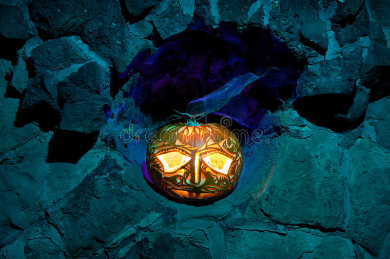 Jack O'lantern in a stone niche. Halloween pumpkin with candle inside in a stone niche stock image